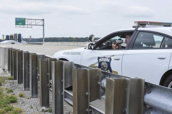 Michelle Davies   The Journal Gazette Indiana State Police Sgt. Brian Walker, PIO for the Indiana State Police Fort Wayne post, monitors speeds on I-469 from Winchester Road Friday afternoon.