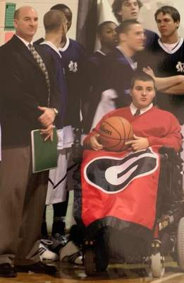 Courtesy Despite having Muscular Dystrophy and using a wheelchair, Michael Johnson led Phil Bollier's Mill Creek team onto the floor before every game in the school's first four years.
