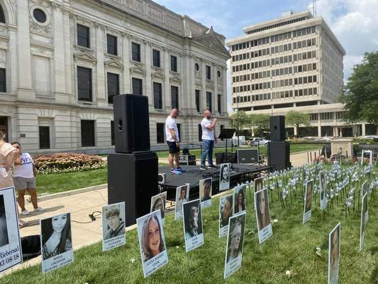 Photos by Jamie Duffy | The Journal Gazette Tommy Streeter, left, and Nate Moellering, both counselors with Bare Knuckle Recovery, speak at Overdose Awareness Day 2021 hosted on the Courthouse Green. Posters of overdose victims were placed on the lawn by family members.