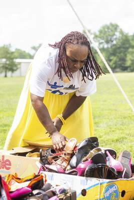 Katie Fyfe | The Journal Gazette  Quamia Jones organizes shoes at the Pie's Clothing Closet booth during 10th annual Community Festival at McMillen Park on Saturday.