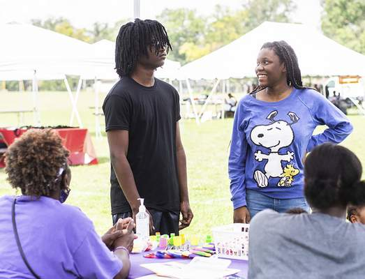 Katie Fyfe | The Journal Gazette Gabriel Boles and Mikaila Boles stop at the Bright Point Group booth during the 10th annual Community Festival at McMillen Park on Saturday.