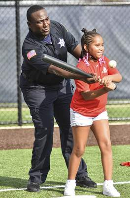 Katie Fyfe | The Journal Gazette  Candace Bates, 9, hits the ball with help from Fort Wayne police Officer James Payne during the Badges for Baseball clinic at ASH Centre on Wednesday.
