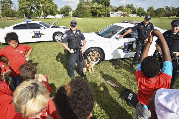 Katie Fyfe | The Journal Gazette Local police talk to kids from the Boys & Girls Club about their K9 units during Badges for Baseball at the Academy of Sports & Health Centre on Wednesday.