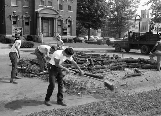 July 19, 1960: A crew cleans up after removing an elm tree and cutting it up into manageable pieces.
