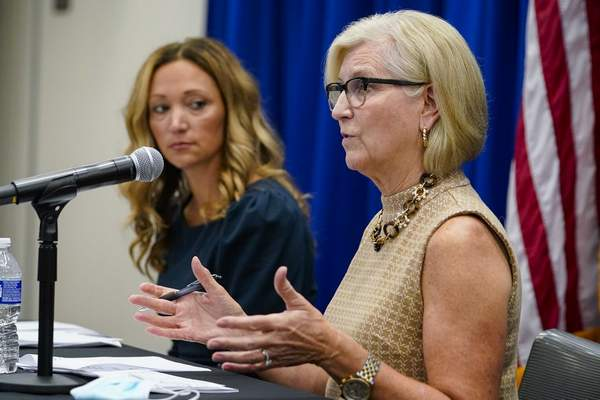 Dr. Kris Box, right, Indiana State Health Commissioner, speaks as Dr. Lindsay Weaver, Indiana Chief Medical Officer, listens during an update on COVID-19 and its impact on Indiana during a media briefing in Indianapolis, Friday, Aug. 27, 2021. (AP Photo/Michael Conroy)