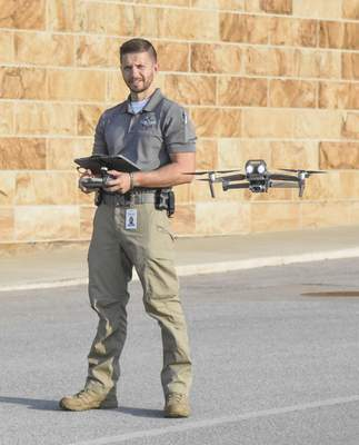 Michelle Davies   The Journal Gazette Officer Trent Hullinger, with the Fort Wayne Police Department's Aerial Support Unit, demonstrates how to operate a drone during a hobbyist drone conference Saturday at Sweetwater Sound.