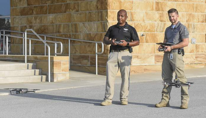 """Michelle Davies   The Journal Gazette FWPD officers Bobby Lemon, left, and Trent Hullinger, right, with The Fort Wayne Police Department Aerial Support Unit (ASU) demonstrate how to operate drones Saturday morning at Sweetwater Sound during the first """"Hobbyist Drone Conference"""". The conference was designed for drone hobbyists and focused on drone safety, rules, and regulations. Lemon is operating a Mavick 2 Pro and Hullinger a Mavick 2 Enterprise Dual."""