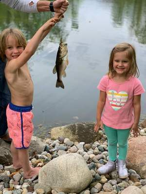 Harrison Huttenlocker, 6, and his sister Sloane Huttenlocker, 4, pose with Harrison's first lured-caught big-mouth bass. Both kids live in Fort Wayne and caught this fish at their grandparents' local subdivision pond in Covington Manor Farms.