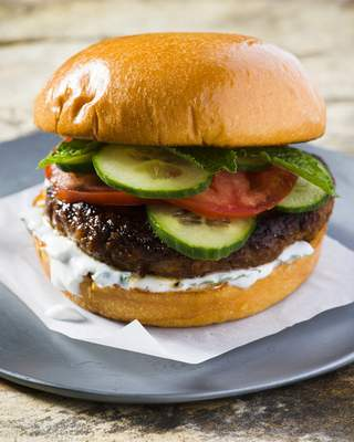 This image released by Milk Street shows a recipe for Indian-spiced pork burgers. The garam masala, cayenne and cumin first are mixed into a paste made from tangy yogurt, egg yolk and breadcrumbs, which helps the burgers stay moist. Mixing the spiced paste into the meat ensures the flavor is distributed evenly throughout each burger. (Milk Street via AP)