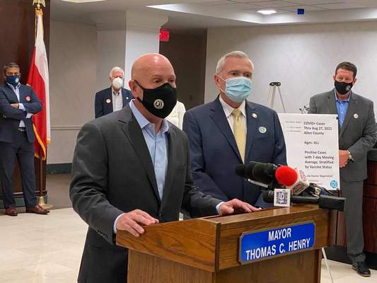 Devan Filchak | The Journal Gazette: Dr. Matthew Sutter, Allen County health commissioner, talks about COVID-19 spread in the community while Fort Wayne Mayor Tom Henry listens at a news conference Thursday. Masks will be required to be worn in all city-owned facilities starting Tuesday.