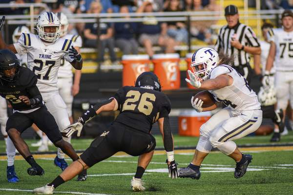 Mike Moore | The Journal Gazette Trine running back Xaine Kirby, right, anticipates the tackle Thursday while running the ball in the first quarter against Manchester in North Manchester.