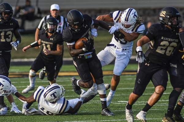 Mike Moore | The Journal Gazette Manchester running back David Smith, center, breaks up the tackle Thursday in the first quarter against Trine.