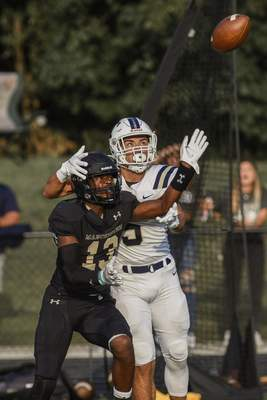 Mike Moore | The Journal Gazette Manchester defensive back Haylee Smith, left, and Trine running back Devonte Jones go up for a pass Thursday in the first quarter at Manchester.