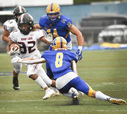 Katie Fyfe | The Journal Gazette  Bishop Luers senior Sir Hale runs the ball while Homestead senior Austin Keezertries to make a tackle during the second quarter at Homestead High School on Friday.