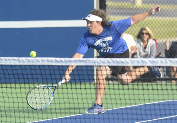 Michelle Davies | The Journal Gazette Canterbury's Oliver VandeWater digs deep as he returns the ball during his doubles match at Saturday's Carroll Invitational.