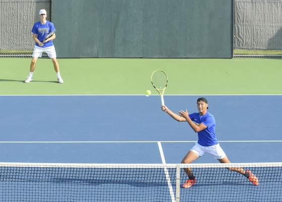 Michelle Davies | The Journal Gazette  Homestead's Alex Graber, right, returns the ball while his partner Matthew Otten, left, keeps an eye on the play during their doubles match at Saturday's Carroll Invitational.