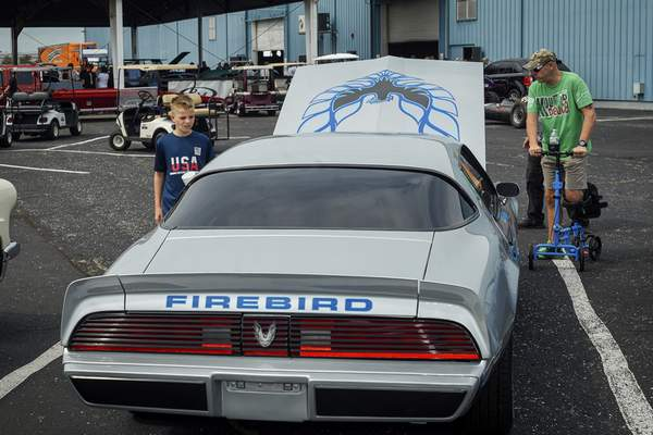 Kayne Holmes, 11, checks out a 1981 Pontiac Firebird with his father, Jamie Holmes, at the Auburn Fall Auction on Saturday.