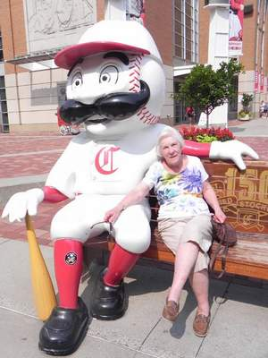Courtesy Linda Kirby Linda Kirby of Fort Wayne sits with Red Stocking outside Great American Ball Park in Cincinnati. She and friend Jerry Hertenstein attended a Cincinnati Reds game this summer. The Reds lost 7-0 to the New York Mets, but Kirby and Hertenstein still enjoyed visiting the city and took a dinner cruise on the Ohio River.
