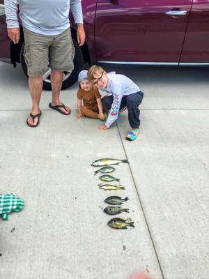 Courtesy Shelley Pulver Ted Pulver took some of his grandchildren fishing at Jimmerson Lake in Angola this summer. Here, Theo Madaras, 8, displays one of the catches. Also pictured is Keanu Madaras, 2. Grandmother Shelley Pulver reports the family was saving all the catches, including those by grandson James Krauss, 9, for a big fish fry.