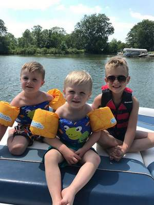 Courtesy Natalie Cagnet Johnny Davis, left, Joey Davis and James Cagnet of Fort Wayne enjoy a boat ride on Big Turkey Lake in Steuben County. Grandmother Natalie Cagnet says summer is a wonderful time for the kids as they boat, fish and explore nature at the lake.