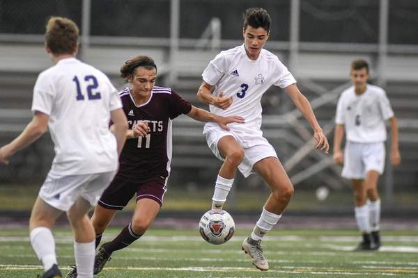 Mike Moore | The Journal Gazette Concordia midfielder Werner Heimlich, left and Bishop Dwenger midfielder Lucas Ciocca fight for the ball in the first half on Tuesday.
