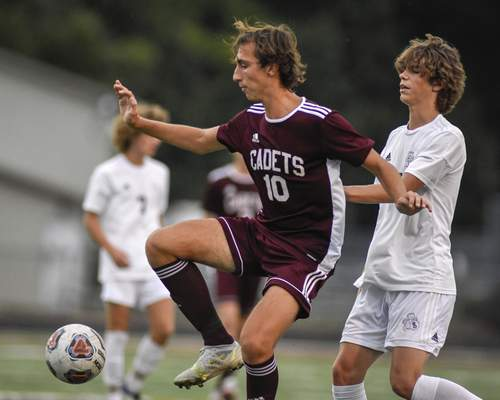 Mike Moore | The Journal Gazette Cadets midfielder Reese Anderson, left, receives a pass Tuesday in the first half against Bishop Dwenger at Zollner Stadium.