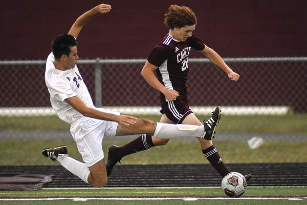 Mike Moore | The Journal Gazette Bishop Dwenger defender Benjamin Kurtzweg, left, tries to take the ball from Concordia forward Isaiah Shutt Tuesday in the first half at Zollner Stadium.