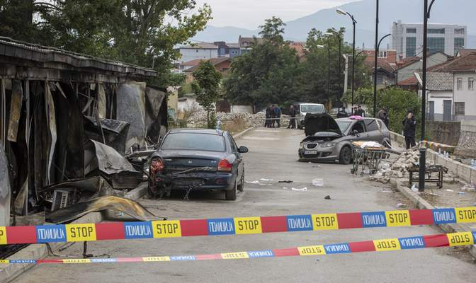 Police officers gather at the site of a destroyed field hospital following a fire in North Macedonia's northwestern city of Tetovo, early Thursday, Sept. 9, 2021. The government of North Macedonia will hold an emergency meeting Thursday over a fire overnight that ripped through a field hospital set up to treat COVID-19 patients, leaving numerous people dead. (AP Photo/Visar Kryeziu)