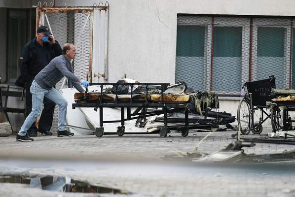 A worker pushes charred beds at the site of destroyed field hospital following a fire in North Macedonia's northwestern city of Tetovo, early Thursday, Sept. 9, 2021. The government of North Macedonia will hold an emergency meeting Thursday over a fire overnight that ripped through a field hospital set up to treat COVID-19 patients, leaving numerous people dead. (AP Photo/Visar Kryeziu)