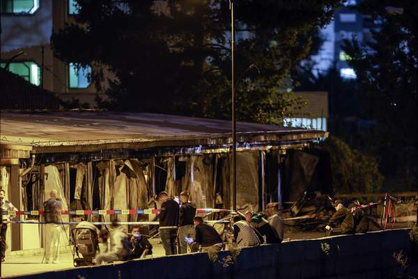 Residents gather as the police officers secure the site of a burned out makeshift hospital following a fire in North Macedonia's northwestern city of Tetovo,Thursday, Sept. 9, 2021. North Macedonia's government has declared three days of mourning after a deadly overnight fire in a COVID-19 field hospital left more than 10 people dead and many injured. The blaze broke out late Wednesday where a hospital had been set up following a recent spike in infections in the region that left local hospitals full. (AP Photo/Visar Kryeziu)