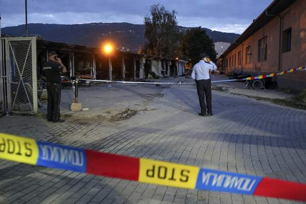 Police officers secure the site of a burned out makeshift hospital following a fire in North Macedonia's northwestern city of Tetovo, Thursday, Sept. 9, 2021. North Macedonia's government has declared three days of mourning after a deadly overnight fire in a COVID-19 field hospital left more than 10 people dead and many injured. The blaze broke out late Wednesday where a hospital had been set up following a recent spike in infections in the region that left local hospitals full. (AP Photo/Visar Kryeziu)