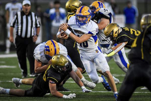 Mike Moore | The Journal Gazette Homestead quarterback Peyton Slaven scrambles for a gain during the second quarter Friday night against Bishop Dwenger. Slaven threw a pair of touchdown passes to Nate Anderson at Shields Field.