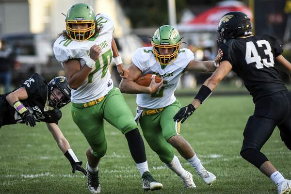 Mike Moore | The Journal Gazette East Side offensive lineman Isaiah Fuentes blocks for quarterback Laban Davis as he runs the ball in the first quarter against Churubusco on Friday.