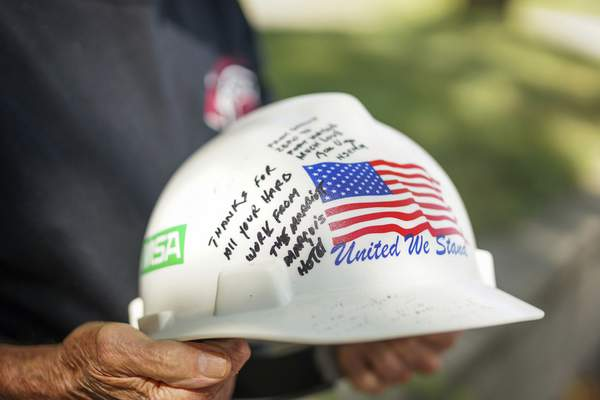 Mike Moore   The Journal Gazette Ed Keller holds the hard hat his late wife, Sarah, wore as a  volunteer in New York after 9/11 that was signed by ground-zero rescue workers.