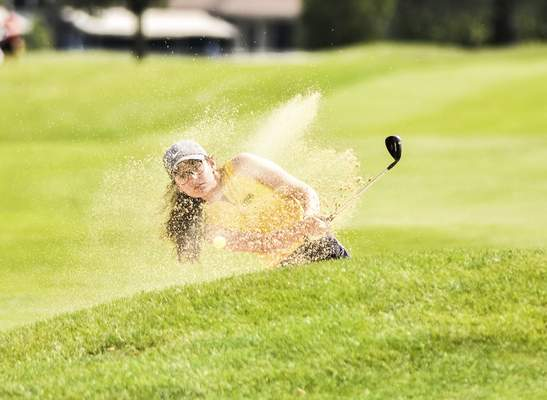 Katie Fyfe | The Journal Gazette Snider senior Mia Birkenbeul hits out of a sand trap onto the green at the first hole during the SAC Girls Golf Tournament at Brookwood Golf Club on Saturday.