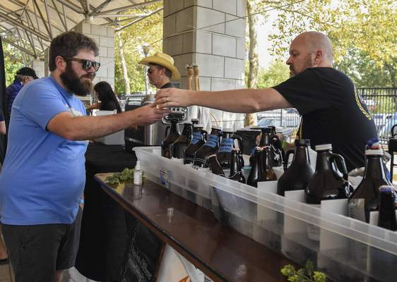 Michelle Davies | The Journal Gazette Matt Elliott of Fort Wayne samples a Colts Kolsch from Mike Heckman with the MASH Fort Wayne Homebrew Club at Saturday's annual Brewed IN the Fort Craft Beer Festival.