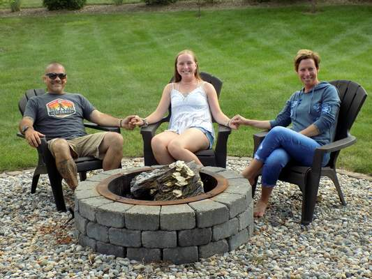Blake Sebring   For The Journal Gazette Sarah Faley sits with her stepfather, Judd Edwards, and mother, Kristi Edwards, in their backyard. Nearly a year ago, Faley was recovering from  brain surgery.
