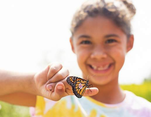 Mya Cadwallader, 8, releases a monarch during Sunday's festival at Eagle Marsh Nature Preserve.