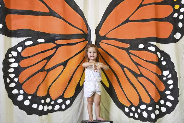 Katie Fyfe | The Journal Gazette Aubree Eyestone, 2, poses for a photo with butterfly wings during the Monarch Festival at Eagle Marsh on Sunday.
