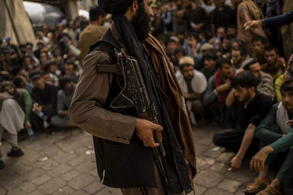 A Taliban fighter controls a crowd waiting to withdraw money from a bank branch in Kabul, Afghanistan, Sunday, Sept. 12, 2021. (AP Photo/Bernat Armangue)
