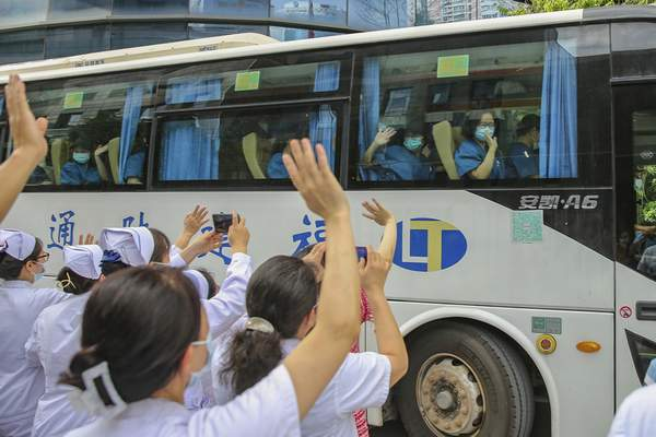 Medical workers send off their colleagues leaving to help with an outbreak of COVID-19 in Putian from a provincial hospital in Fuzhou in southeast China's Fujian province Sunday, Sept. 12, 2021. (Chinatopix via AP)