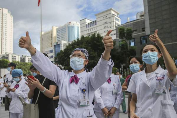 Medical workers give thumbs-up to their colleagues leaving to help with an outbreak of COVID-19 in Putian from a provincial hospital in Fuzhou in southeast China's Fujian province Sunday, Sept. 12, 2021. (Chinatopix via AP)