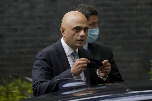 FILE - In this Wednesday, June 30, 2021 file photo, Britain's newly appointed Health Secretary Sajid Javid looks at photographers as he puts on a face mask to curb the spread of coronavirus as he gets into his ministerial vehicle after leaving 10 Downing Street in London. (AP Photo/Matt Dunham, File)