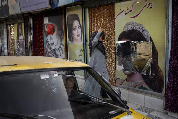 Associated Press An Afghan woman walks past beauty salons with defaced window decorations Sunday in Kabul.