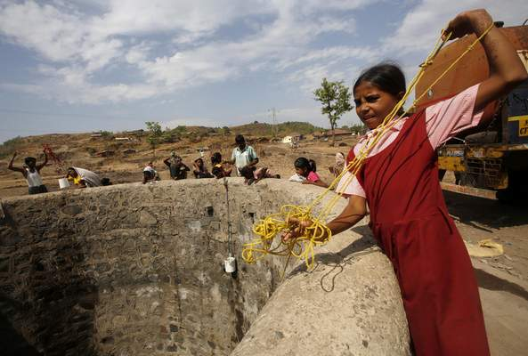 FILE - In this May 4, 2016, file photo, a girl wearing her school uniform pulls a rope attached to a bucket as she tries to draw water after a tanker emptied water into a dried up well at Umber Maal village in Thane district in Maharashtra state, India. (AP Photo/ Rajanish Kakade, File)