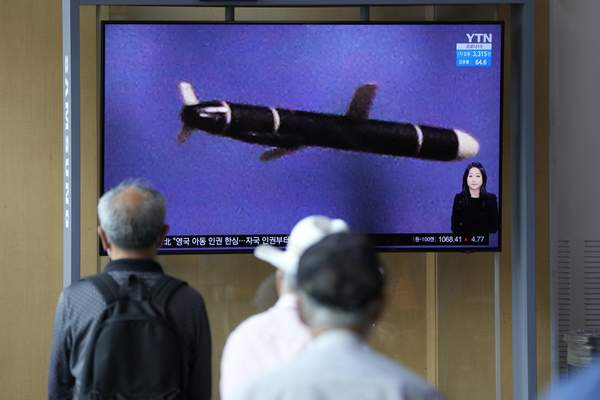 People watch a TV screen showing a news program showing a North Korean handout photo that says, North Korea's long-range cruise missiles tests, in Seoul, South Korea, Monday, Sept. 13, 2021. (AP Photo/Lee Jin-man)