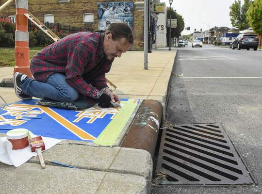 Michelle Davies | The Journal Gazette Scott Eastom of Fort Wayne works on his Clean Drains Fort Wayne project Monday morning along Wells Street. The project is being used to raise awareness about keeping pollutants out of storm drains to protect rivers.