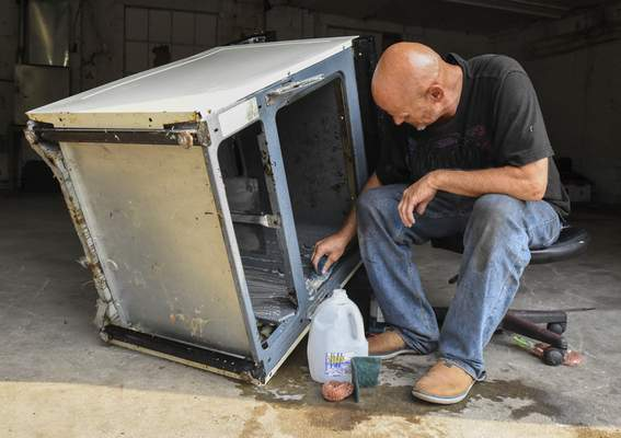 Michelle Davies   The Journal Gazette Fort Wayne resident Randy Olry, owner of Jack of All Trades Appliance & Electronics Repair, cleans an oven Monday morning at his business along Spring Street.