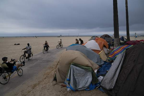 FILE - In this June 29, 2021, file photo people ride their bikes past a homeless encampment set up along the boardwalk in the Venice neighborhood of Los Angeles. (AP Photo/Jae C. Hong, File)