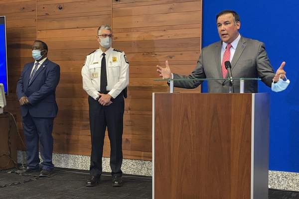 FILE - In this Wednesday, April 21, 2021, file photo, Columbus Mayor Andrew Ginther, right, speaks during a news conference about the Tuesday fatal police shooting of 16-year-old Ma'Khia Bryant, as she swung a knife at two other people in Columbus, Ohio. (AP Photo/Andrew Welsh-Huggins, File)